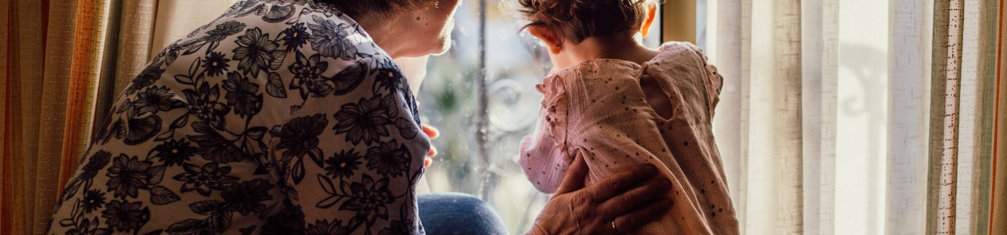 Older woman and a younger child looking out the window