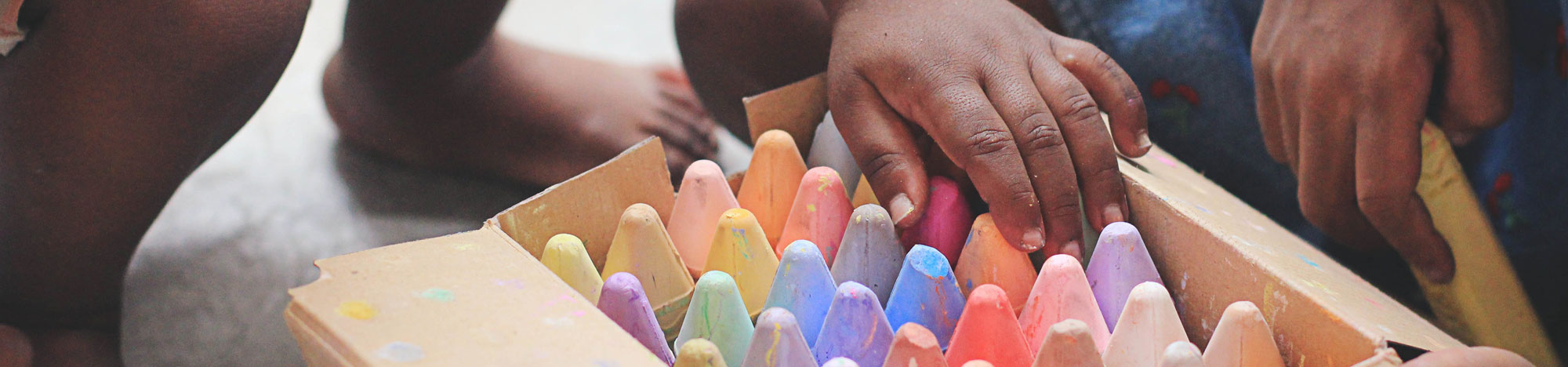Child choosing coloured chalk from a box